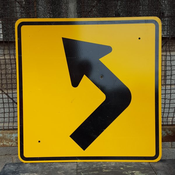 Black left pointing arrow, yellow road sig